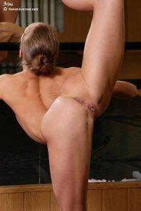 На фото голая балерина делает разминку