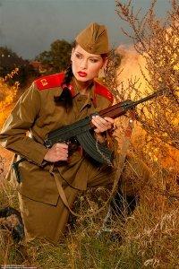 На фото девушка в форме защищает Родину